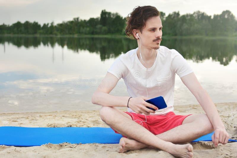 Mann sitzt auf dem Strand am See und hört Musik stockfotografie