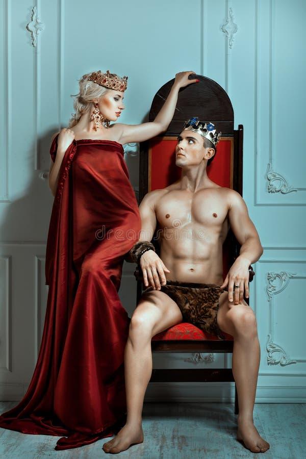 Mann sitzt auf dem Thron und betrachtet Königin stockfotografie