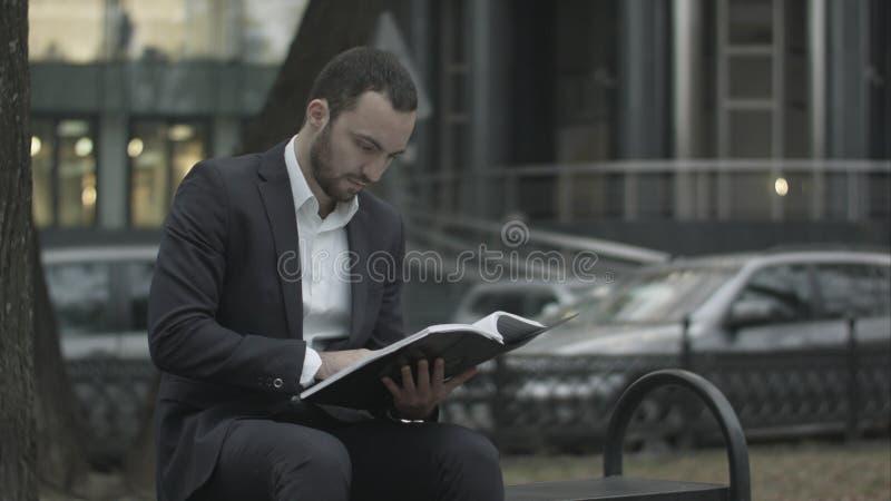 Mann sitzt auf einer Bank im Park und liest anerkennend Unternehmensplan, Geschäftspapiere stockfoto