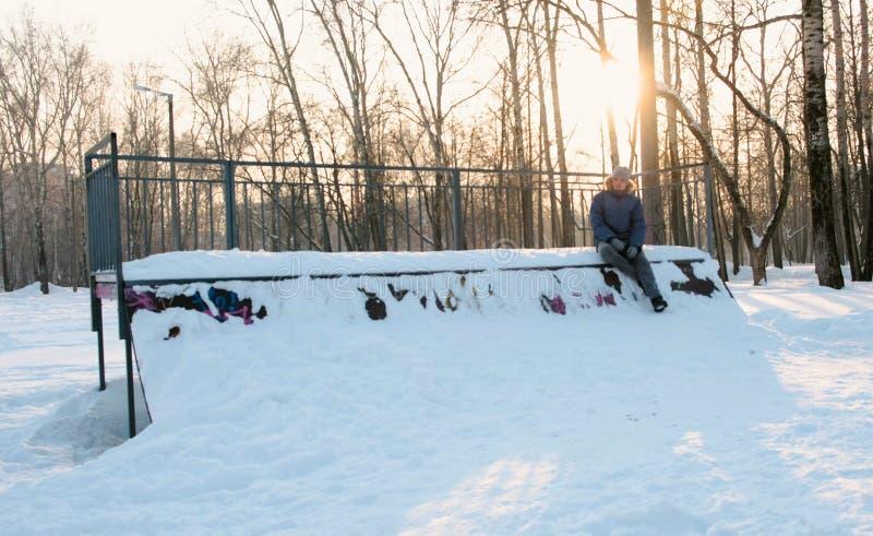 Mann sitzt auf Rocheneinstiegpark im Schnee Schneeantriebe auf dem Hügel zum Skateboard zu fahren unschärfe stockfotos