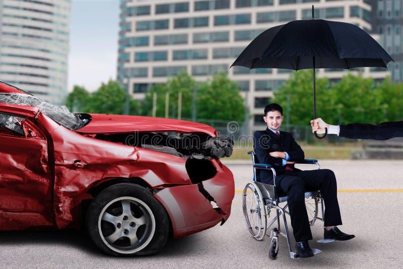 Mann sitzt auf Rollstuhl mit beschädigtem Fahrzeug stockfoto