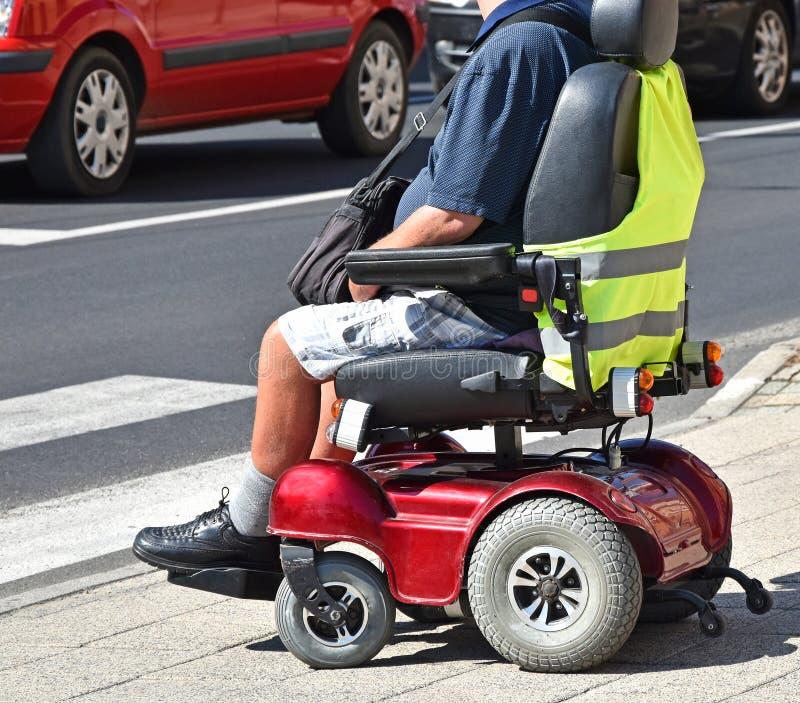 Mann sitzt in einem elektrischen Rollstuhl lizenzfreie stockbilder