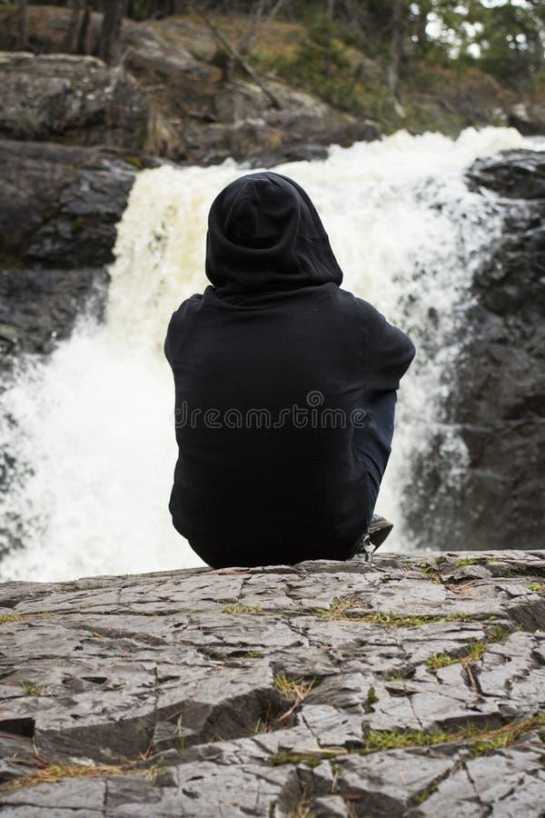 Mann sitzt friedlich am ruhigen Wasserfall lizenzfreie stockfotos