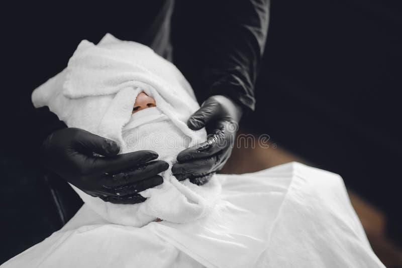 Mann sitzt im Friseursalonstuhl und dämpft sein Gesicht mit heißem Tuch vor dem königlichen Bart, der Rasiermesser rasiert lizenzfreie stockfotos