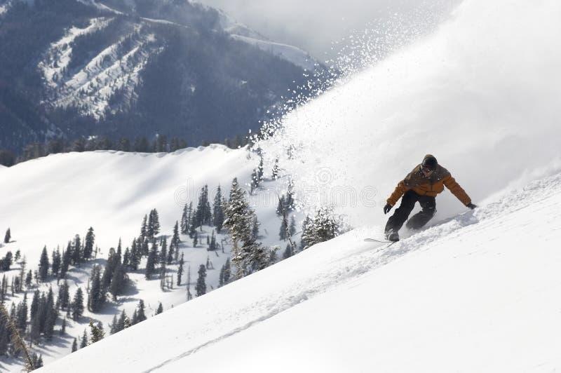 Mann-Snowboarding-unten Hügel stockbild