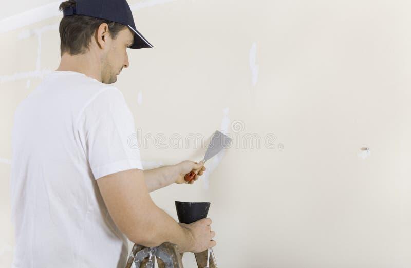 Mann Spacklessprünge in der Wand stockbilder