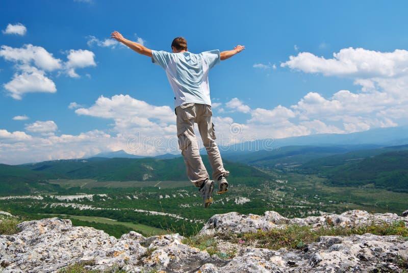 Mann springen vom Berg lizenzfreie stockfotos