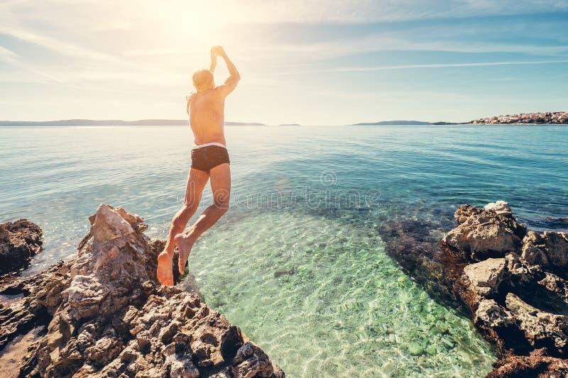 Mann springt in klares Kristallwasser auf adriatisches Seebucht lizenzfreies stockbild