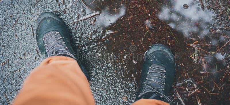 Mann staingg bei regnerischem Herbstwetter in einer Pfütze in wasserdichte Spurhaltungsschuhe Fallwetter Konzept Ganzjähriges Abe stockfoto