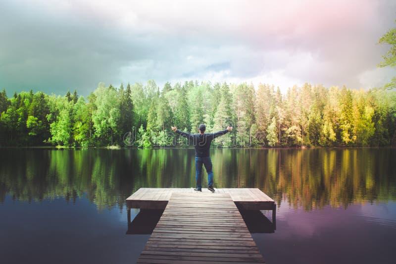 Mann steht auf dem Pier von einem schönen See, der junge Mann, der das Leben, seine Arme genießt, sich öffnen, ein Regenbogen übe lizenzfreie stockfotos