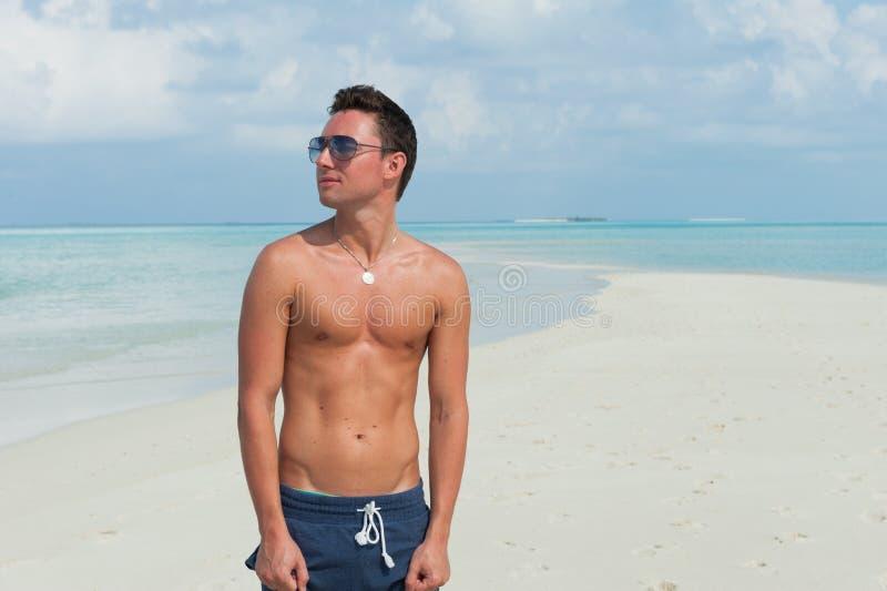 Mann steht auf dem Strand mit dem blauen Meer und dem schönen Himmel lizenzfreie stockbilder