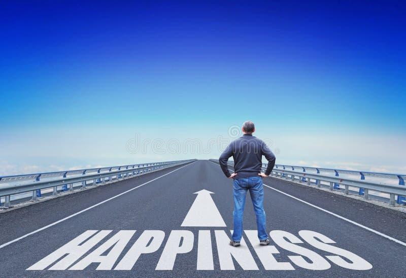 Mann steht auf einer Straße, die zum Glück geht stockfotografie