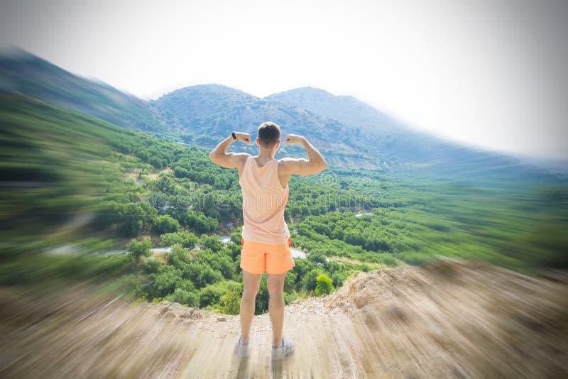 Mann steht in der Siegerhaltung auf die Oberseite eines Berges Das Konzept der Führung, der Stärke, des Vertrauens und der Freihe stockbild