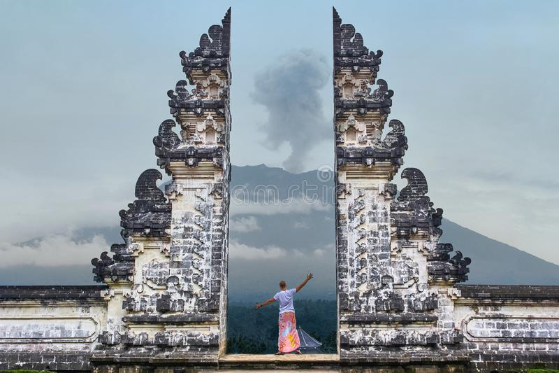 Mann steht im Tor von Lempuyang-Tempel auf Bali-isalnd, Indonesien lizenzfreie stockfotos