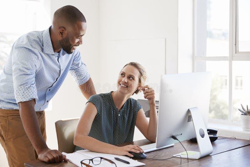 Mann steht, sprechend mit der Frau, die an ihrem Schreibtisch in einem Büro lächelt stockbilder