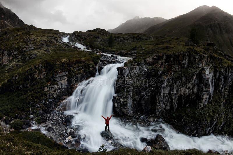 Mann steht unter einem Gebirgswasserfall im nebelhaften Tal von Island stockfotografie