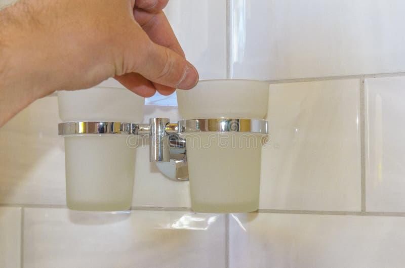 Mann stellt die Schalen im Halter im Badezimmer, im Konzept der Reparatur und im Heimwerken ein lizenzfreies stockfoto