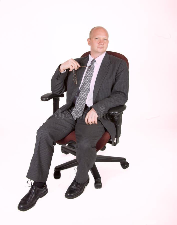 Mann in Stuhl-Holding-Gläsern 02 stockbild