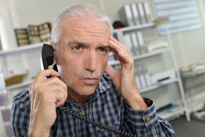 Mann am Telefon, das betroffen schaut lizenzfreie stockbilder