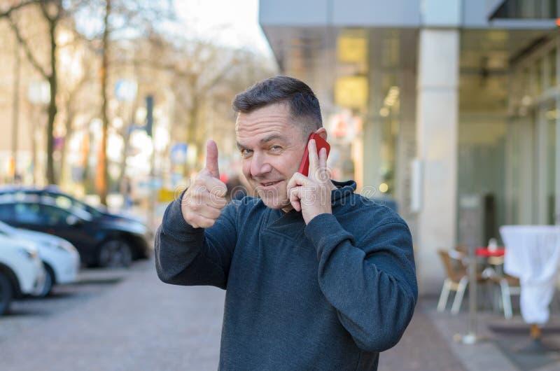 Mann am Telefon, das sich Daumen zeigt stockfotografie