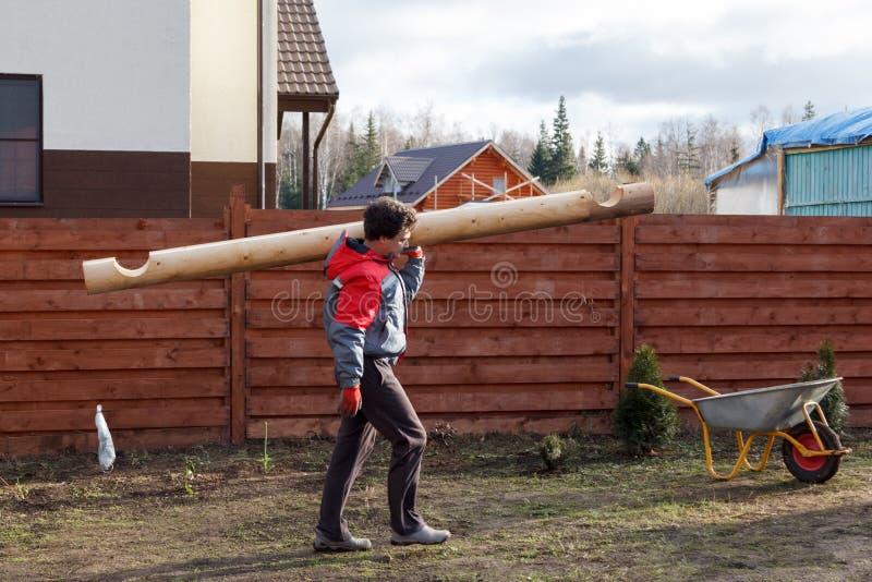 Mann trägt Klotz, um eine hölzerne Laube zu errichten lizenzfreie stockfotos