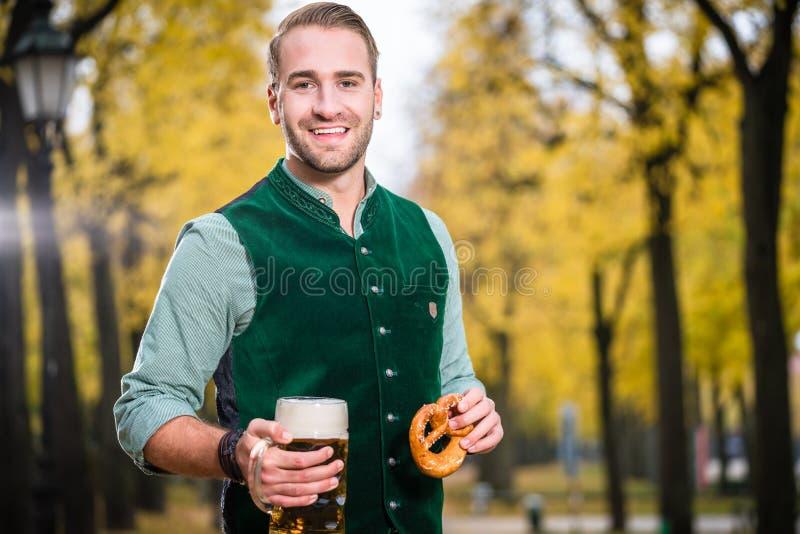 Mann in traditionellem bayerischem trinkendem Bier Tracht aus enormem Becher heraus lizenzfreie stockfotos