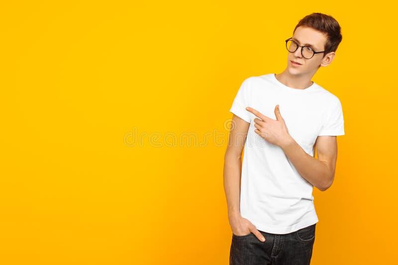 Mann, tragende Gläser, im weißen leeren T-Shirt, zeigend mit zwei Fingern auf die Seite, die zeigt, um Raum, auf gelbem Hintergru lizenzfreies stockbild