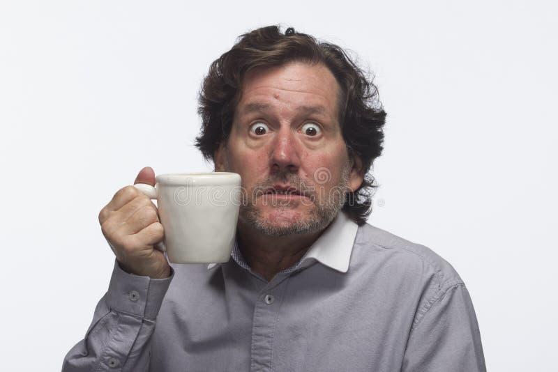 Mann trank zu viel Kaffee (Becher halten), horizontal lizenzfreie stockfotos