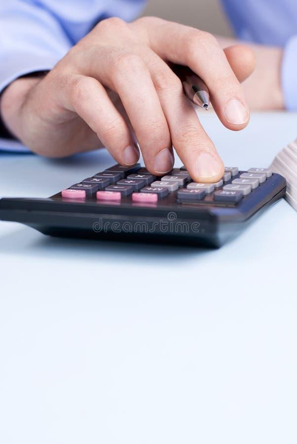 Hand und ein Taschenrechner stockfotos