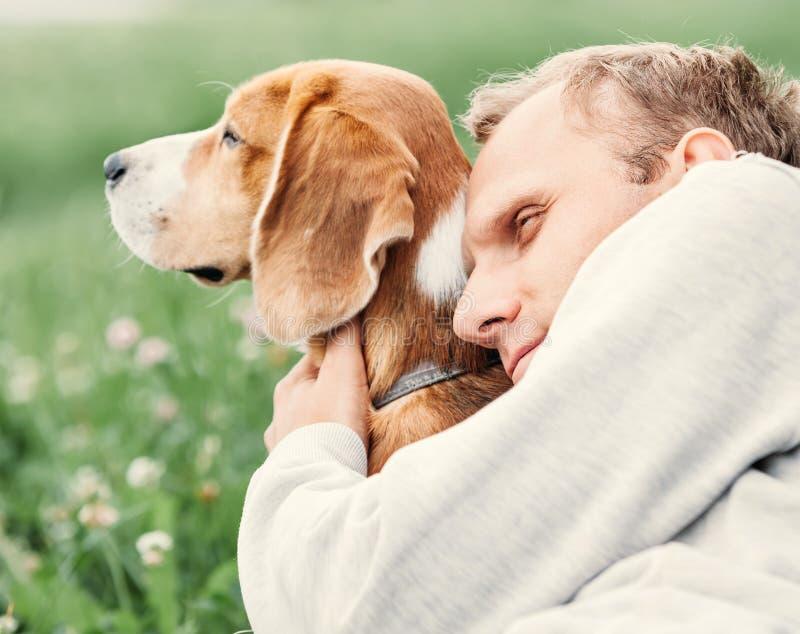 Mann umarmt seinen Lieblingshund lizenzfreie stockbilder