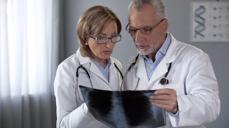Mann und Ärztinnen, die den Lungeröntgenstrahl, Pneumoniediagnose besprechend betrachten stockbilder