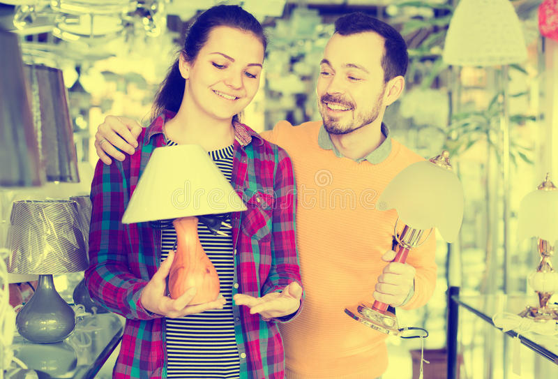 Mann und ein Mädchen überprüfen die Wahlen für Lampen lizenzfreie stockfotos