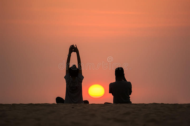 Mann und Frau auf dem Hintergrund des schönen Sonnenuntergangs Yoga und der Fotograf sitzen auf dem Strand, um den Sonnenuntergan lizenzfreie stockfotografie
