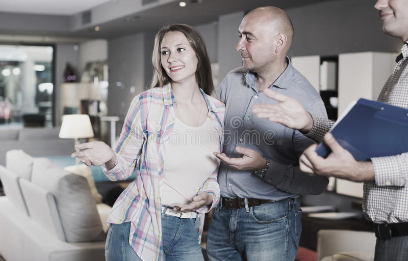Mann und Frau beraten sich mit Verkäufer, um neues Sofa zu wählen lizenzfreie stockfotografie