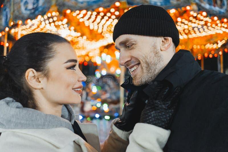 Mann und Frau an der Weihnachtsmesse, die einander und das Lächeln betrachtet Selfie lizenzfreie stockfotos