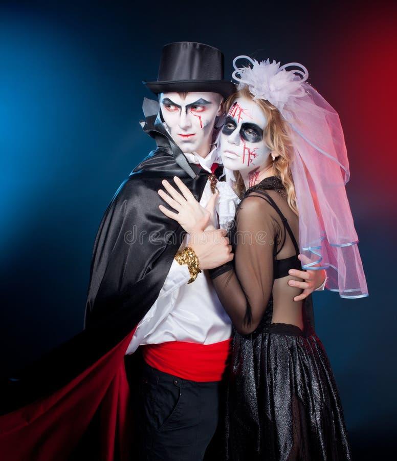 Mann und Frau, die als Vampir und Hexe tragen. Halloween stockfotografie