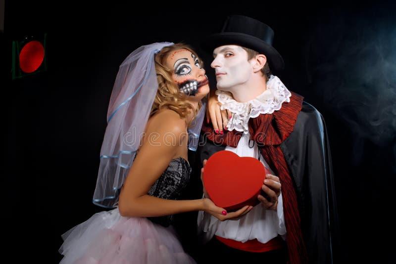 Mann und Frau, die als Vampir und Hexe tragen. Halloween stockbild