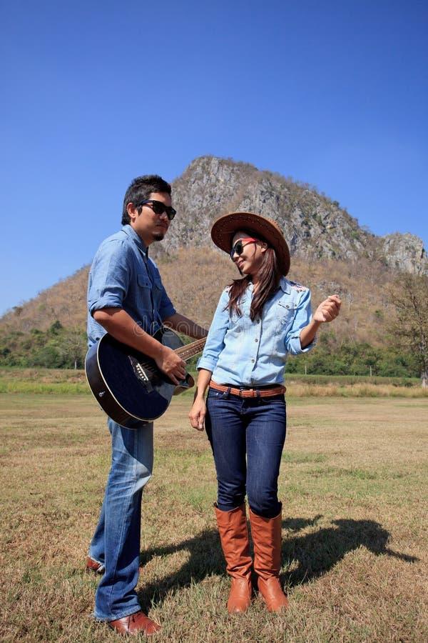 Mann und Frau, die auf dem Bauernhofgebiet spielt Gitarre und das Tanzen steht stockfotografie