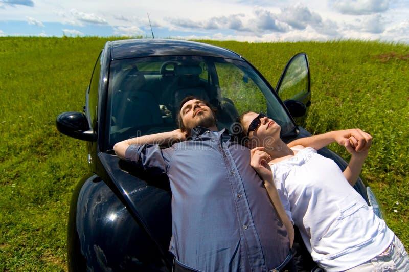 Mann und Frau, die auf einem Auto sich entspannen lizenzfreies stockfoto