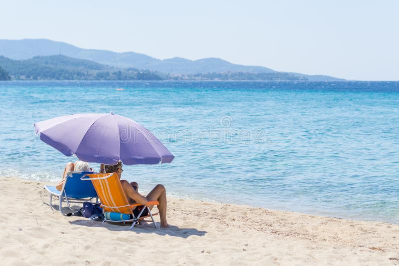 Mann und Frau, die auf kleinen Faltstühlen auf dem Strand unter purpurrotem Sonnenschutz mit Blick auf das blaue Meerwasser sitze lizenzfreie stockbilder