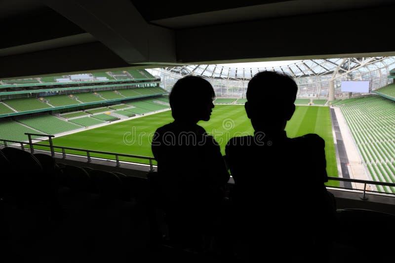 Mann und Frau, die auf Stadion stehen und sprechen lizenzfreie stockbilder