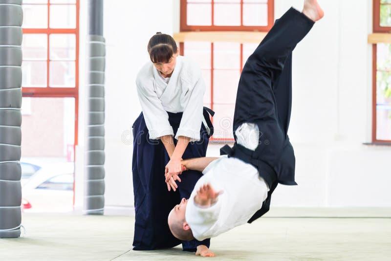 Mann und Frau, die an der Aikidokampfkunstschule kämpfen lizenzfreies stockfoto