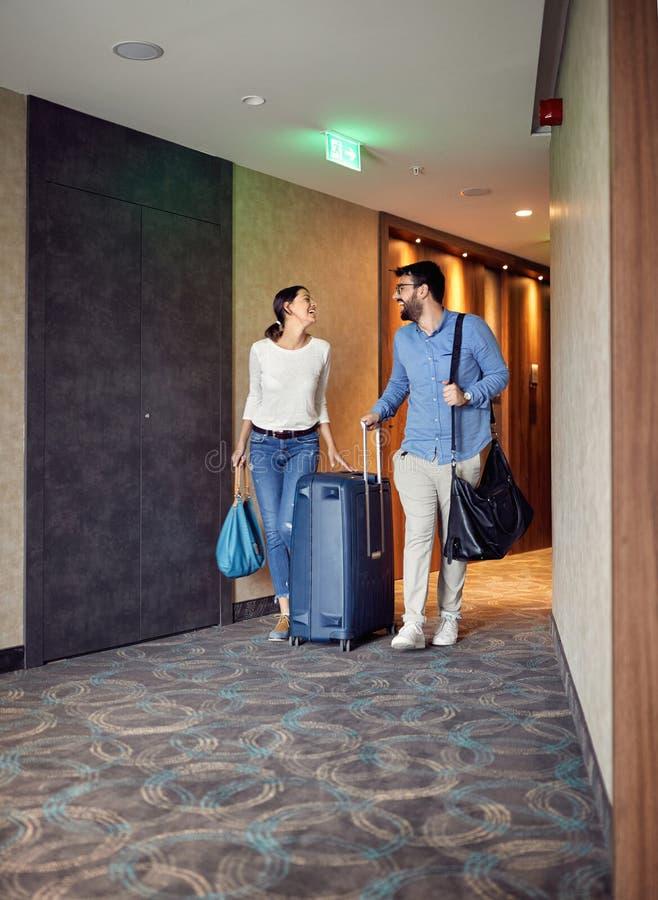 Mann und Frau, die in der Hotellobby mit Koffer ankommen lizenzfreie stockbilder
