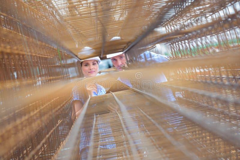Mann und Frau, die durch Stapel Rebars schauen stockfoto