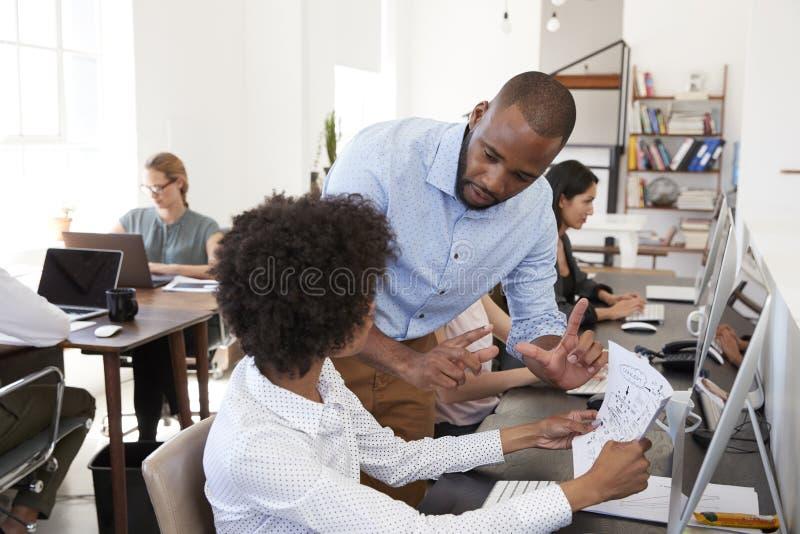 Mann und Frau, die an einem Schreibtisch im Bürogroßraum zusammenarbeiten stockbild