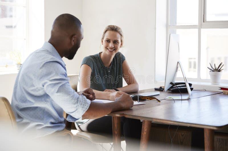 Mann und Frau, die an einem Schreibtisch spricht in einem Bürolächeln sitzt stockfoto