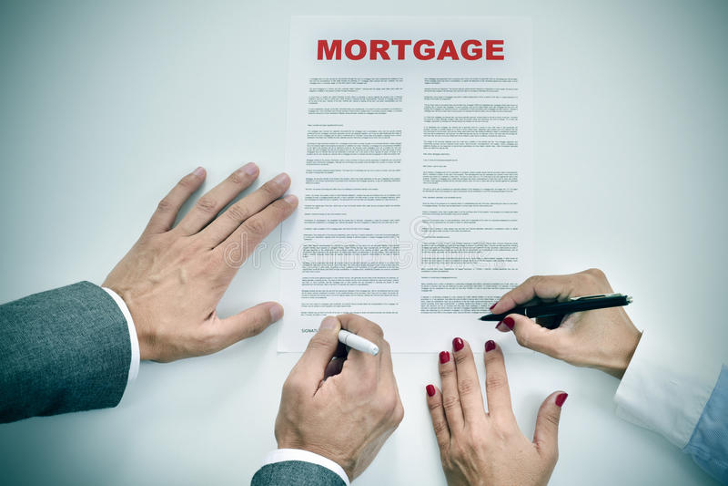 Mann und Frau, die einen Hypothekendarlehendarlehensvertrag unterzeichnen stockfoto
