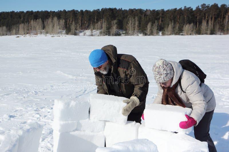 Mann und Frau, die einen Iglu in der schneebedeckten Lichtung, Nowosibirsk, Russland errichten stockbild