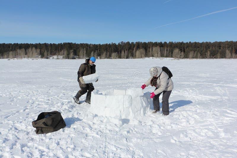 Mann und Frau, die einen Iglu in einer schneebedeckten Lichtung errichten stockfoto
