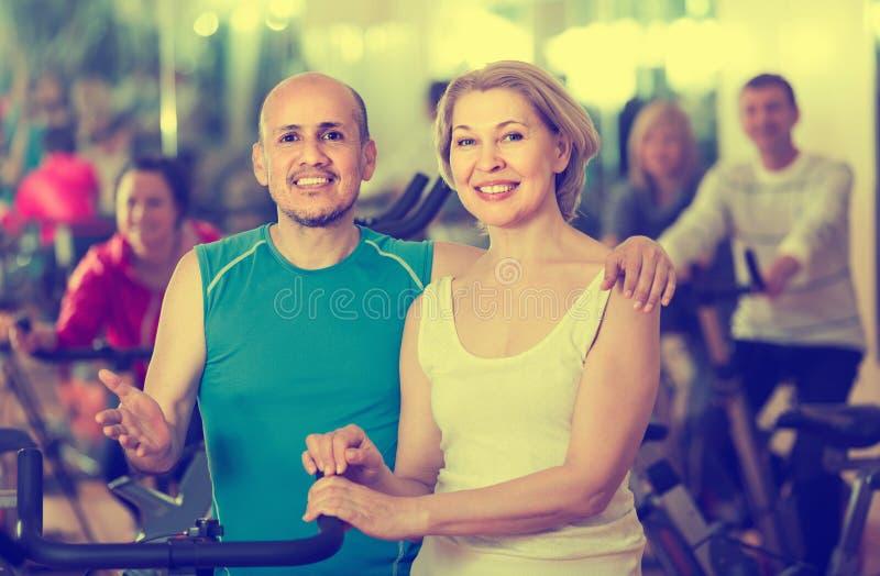 Mann und Frau, die in einer Turnhalle und in einem Lächeln aufwerfen stockbild